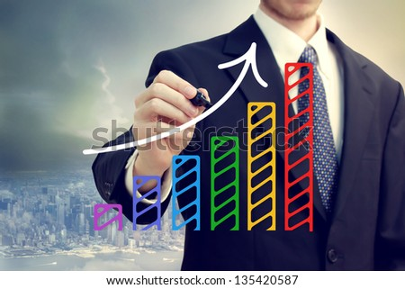 Businessman drawing a rising arrow over a bar graph above the city - stock photo