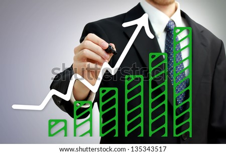 Businessman drawing a rising arrow over growing green bar graph - stock photo