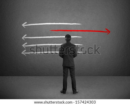 Businessman drawing arrows in different directions - stock photo