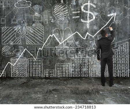 businessman drawing business concept doodles on old concrete wall and mottled floor background - stock photo