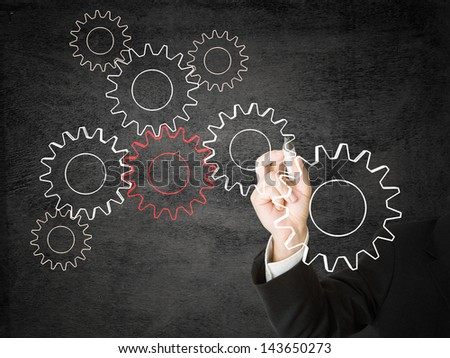 Businessman drawing cogwheels - networking or cooperation concept - stock photo