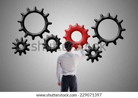 Businessman drawing gear wheels - stock photo