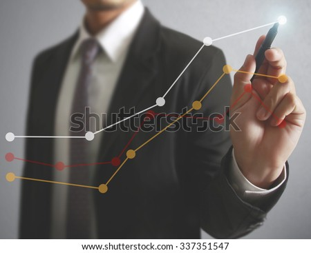 Businessman drawing graphics a growing graph - stock photo