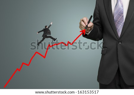 Businessman drawing growth red arrow and another jumping on it, leadership and team work concept - stock photo