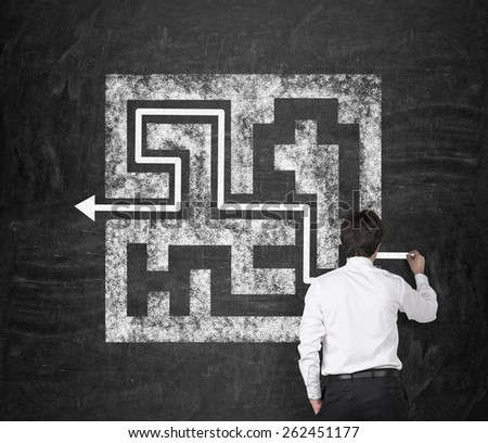 businessman drawing labyrinth with arrow on wall - stock photo