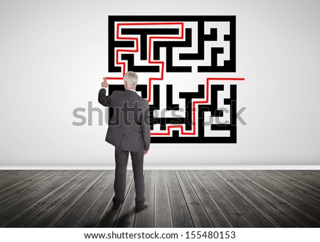 Businessman drawing line through quick response code on a wall - stock photo