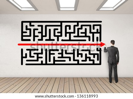 businessman drawing maze on wall in room - stock photo