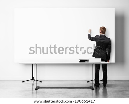 Businessman drawing on flip chart - stock photo