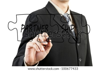 Businessman drawing partnership puzzle pieces - stock photo