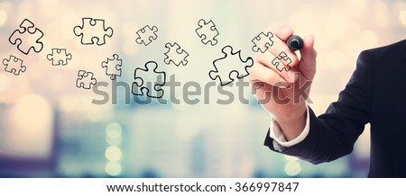 Businessman drawing Puzzles concept on blurred abstract background  - stock photo