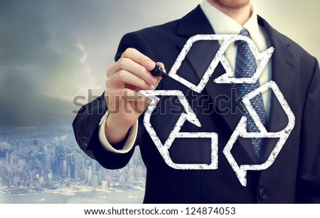 Businessman drawing recycle sign in the city - stock photo
