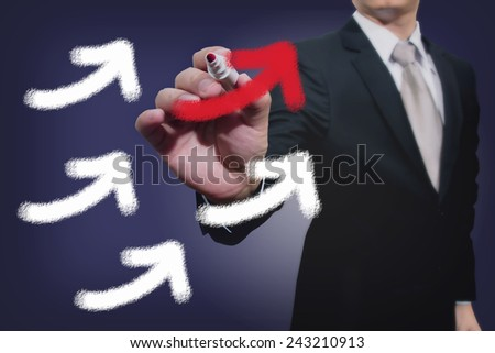 Businessman drawing rising arrows - stock photo