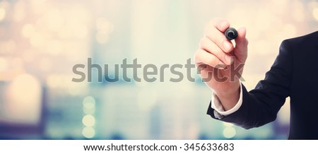 Businessman drawing something with a black maker on blurred abstract background - stock photo