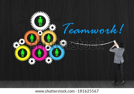 Businessman drawing teamwork with gear and employee symbol on black wall - stock photo