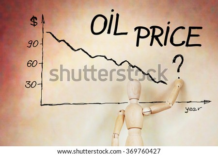 Businessman draws the graph of oil price fall. Abstract image with a wooden puppet - stock photo