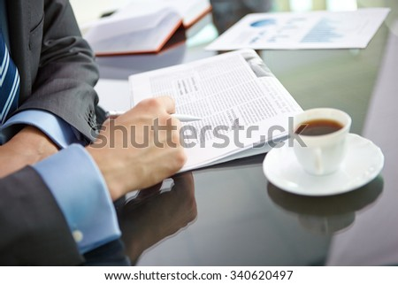 Businessman drinking coffee and reading newspaper - stock photo