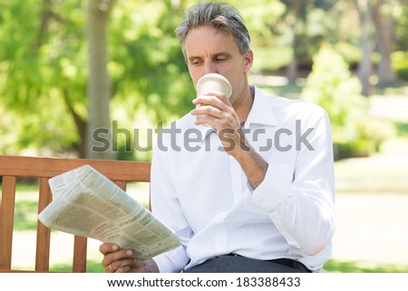 Businessman drinking coffee while reading newspaper in the park - stock photo