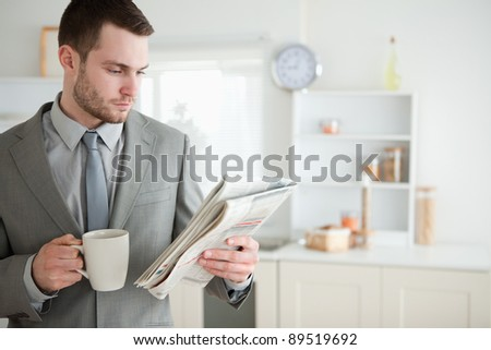 Businessman drinking coffee while reading the news in his kitchen - stock photo
