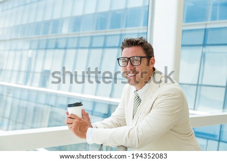 Businessman drinking coffee while standing at window - stock photo