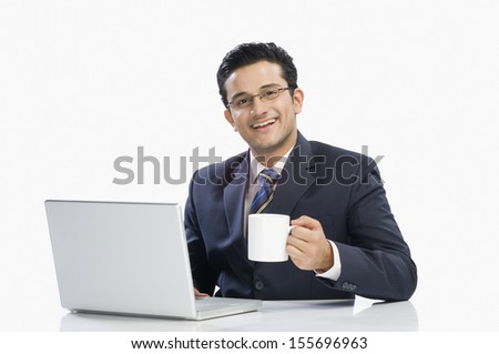 Businessman drinking coffee while working on a laptop - stock photo