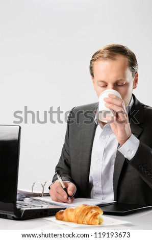 Businessman drinks coffee while working hard signing documents and contracts - stock photo