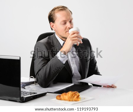 Businessman drinks enjoys his morning coffee and croissant before he starts work - stock photo