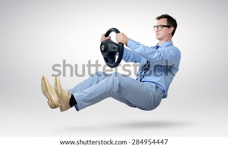 Businessman driver in glasses and tie with a wheel - stock photo