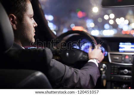 businessman driving a car at night - stock photo