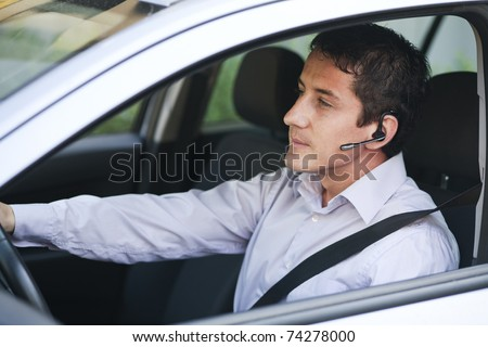 Businessman driving a car with blue-tooth hands-free - stock photo