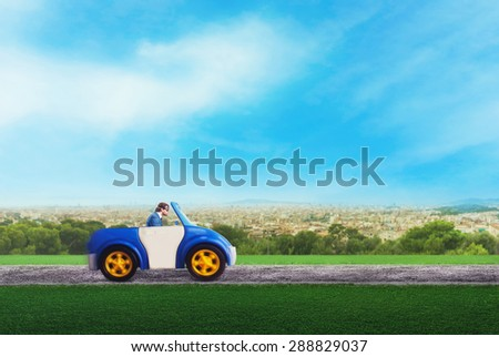 Businessman driving a toy car - stock photo