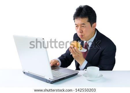 businessman eating hamburger while working, isolated on white background. - stock photo
