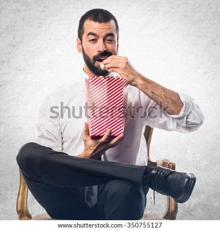 Businessman eating popcorns - stock photo