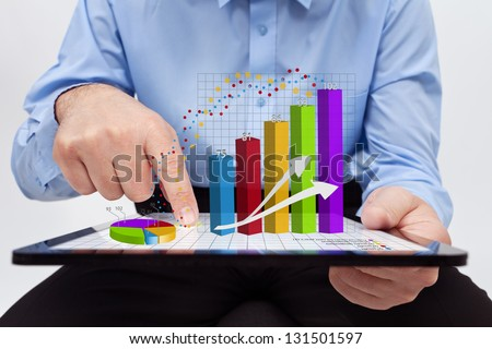 Businessman editing the annual report charts - working on a tablet computer - stock photo