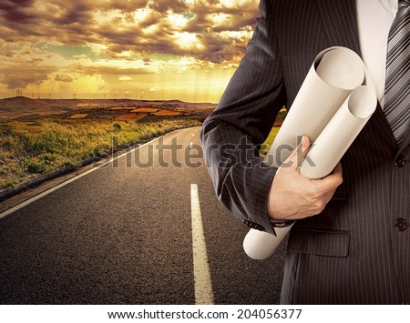 Businessman engineer holding blueprints of new architectural project standing on straight road. Concept of successful career start.  - stock photo