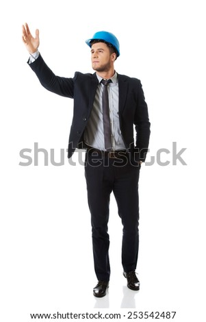 Businessman engineer in hard hat showing copyspace. - stock photo