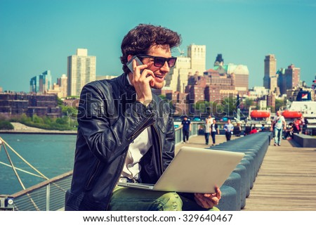 Businessman enjoying working on site. Wearing leather jacket, sunglasses, a guy with beard, sitting on bench at harbor, working on laptop computer, talking on phone in the same time. Instagram effect. - stock photo