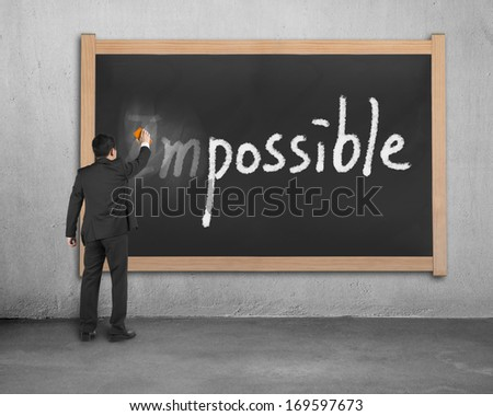 Businessman erasing impossible word on dirty wooden chalk board in concrete background - stock photo