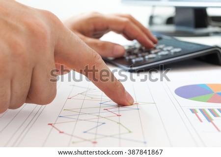 Businessman examining financial charts using a calculator - stock photo