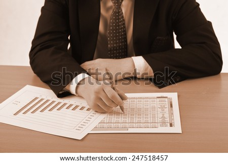 Businessman examining graphs at desk in his office - vintage effect - stock photo