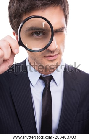 Businessman examining you. Serious young man in formalwear examining you with magnifying glass while standing isolated on white background  - stock photo