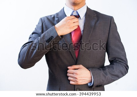 Businessman Executive adjusting red tie, isolated on white background - stock photo