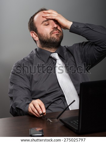 Businessman exhausted at work in his office. - stock photo