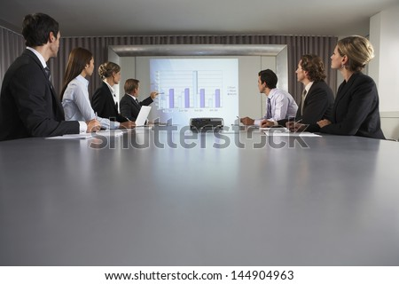 Businessman explaining bar chat to colleagues at conference table - stock photo