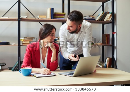 businessman explaining something to woman and looking at her, woman listening and looking at laptop in office - stock photo