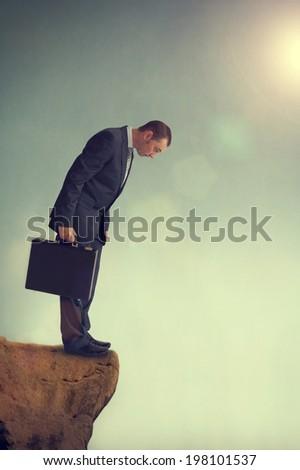 businessman facing a dilemma on a cliff edge - stock photo