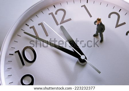 Businessman figurine standing on a huge clock - stock photo