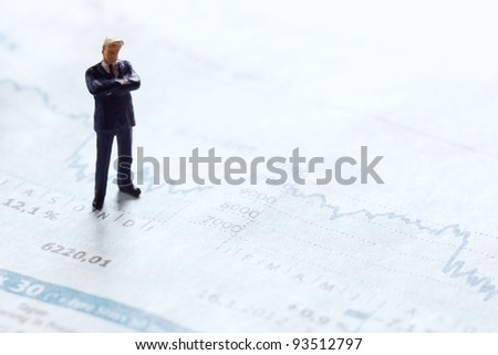 businessman figurine standing upon a financial sector of a newspaper - stock photo