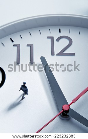 Businessman figurine walking on a huge clock - stock photo