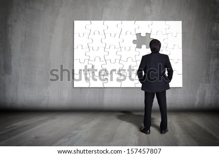 Businessman figuring out puzzle pieces with piece missing on grey wall - stock photo