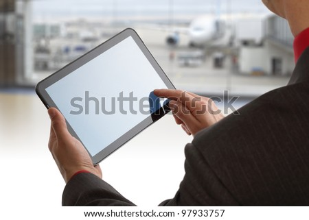 Businessman finger touching screen of a digital tablet at the departure gate of an airport - stock photo